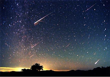 弧を描く星と飛び交う流れ星